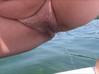 My wife peeing again from a pedal boat into the lake