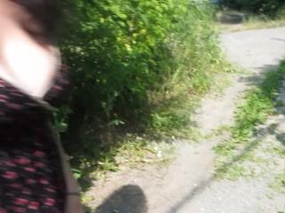 Mature brunette Milf pisses raising a dress on a path in a public place